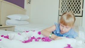 Een 6 éénjarigenmeisje met een hotelarmband op haar hand speelt met bloembloemblaadjes Op haar is het bed een hart van handdoeken stock footage
