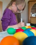 Een 7 éénjarigenmeisje schildert eieren voor Pasen royalty-vrije stock afbeelding