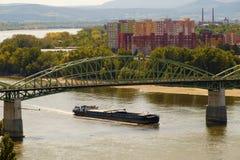 Een aak die onder de brug varen die Sturovo in Slowakije verbinden stock afbeelding