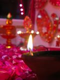 Een aangestoken diya op bed van rozen Royalty-vrije Stock Afbeelding