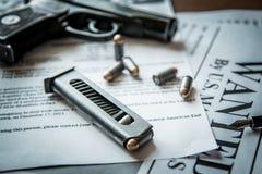 Een aankondiging over het onderzoek naar een misdadiger op de lijst van de gulle giftjager, een gevechtspistool, patronen Stock Afbeelding
