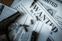 Een aankondiging over het onderzoek naar een misdadiger op de lijst van de gulle giftjager, een gevechtspistool, patronen Stock Foto