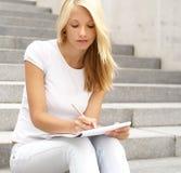 Een aantrekkelijk blond meisje schrijft een nota Stock Afbeeldingen