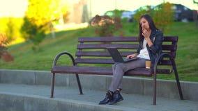 Een aantrekkelijk jong meisje, eet een broodje en werkt bij laptop stock footage