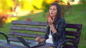 Een aantrekkelijk jong meisje, eet een broodje en werkt bij laptop stock videobeelden