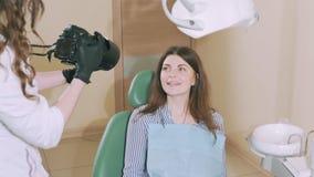 Een aantrekkelijk, aantrekkelijk jong meisje in het tandarts` s bureau glimlacht ruim en toont het resultaat van de tandarts ` s stock videobeelden