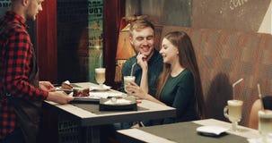 Een aantrekkelijk jong paar rust in een koffie stock video