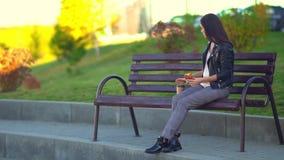 Een aantrekkelijk meisje in het Park op een bank die een broodje eten en koffie drinken stock footage