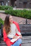 Een aantrekkelijk meisje met lang bruin haar en een witte tandglimlach zit op een bank en schrijft haar gedachten op de stedelijk royalty-vrije stock afbeelding