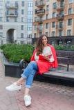 Een aantrekkelijk meisje met lang bruin haar en een witte tandglimlach zit op een bank en schrijft haar gedachten op de stedelijk stock foto's
