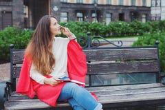 Een aantrekkelijk meisje met lang bruin haar zit op een bank, verbergend achter een rode deken, knagend aan een pen en denkend op royalty-vrije stock afbeelding