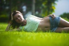 Een aantrekkelijk meisje met een prettige glimlach en een donker lang haar ligt op het groene gras Het vrij gelukkige meisje geni stock fotografie