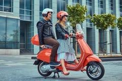 Een aantrekkelijk paar, een knappe mens en een sexy wijfje die samen op een rode retro autoped in een stad berijden stock foto