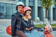 Een aantrekkelijk paar, een knappe mens en een sexy wijfje die samen op een rode retro autoped in een stad berijden stock foto's