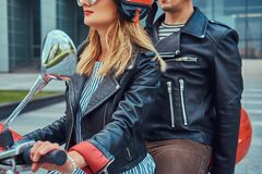 Een aantrekkelijk paar, een knappe mens en een sexy wijfje die samen op een rode retro autoped in een stad berijden stock fotografie