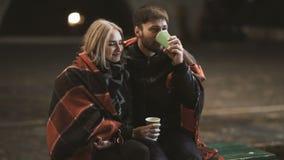 Een aantrekkelijk paar in liefde omhelst en geniet van een vertrouwelijk ogenblik samen, tegen de achtergrond van stadslichten stock videobeelden