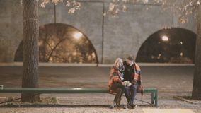 Een aantrekkelijk paar in liefde omhelst en geniet van een vertrouwelijk ogenblik samen, tegen de achtergrond van stadslichten stock video