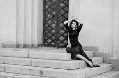 Een aantrekkelijk sexy slank brunette in een lange zwarte kleding met een spleetzitting op de stappen van een uitstekend gebouw Royalty-vrije Stock Foto