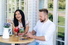 Een aantrekkelijk vrolijk meisje kwam een aardige modieuze kerel zien een paar rust in een koffie, etend matrijzen, die spreken e royalty-vrije stock afbeelding