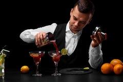 Een aantrekkelijke barman giet een cocktail in een glas van Margarita, sinaasappelen, citroen, plakken van kalk op een zwarte ach Stock Fotografie