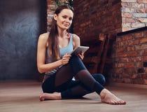 Een aantrekkelijke donkerbruine vrouw in een ruimte met zolderbinnenland Stock Foto