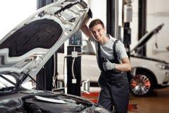 Een aantrekkelijke jonge autowerktuigkundige glimlacht: de autodienst en onderhoud royalty-vrije stock foto's