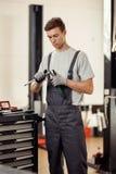 Een aantrekkelijke jonge mens die speciale instrumenten in zijn handen houden is bij het werk in de autodienst stock foto