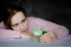Een aantrekkelijke jonge vrouw bekijkt vastbesloten de kinderwagen in haar hand Een groen kinderwagenstuk speelgoed De wandelwage stock foto