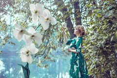 Een aantrekkelijke jonge vrouw in een lange groene kleding bevindt zich op de rivierbank naast witte reuze kunstmatige orchideeën stock foto
