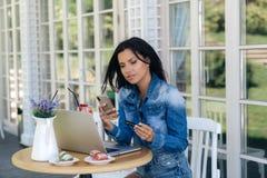 Een aantrekkelijke jonge vrouw maakt een online orde, gebruikt een telefoon, laptop en haar betaalpas voor dit, betaalt haar stock afbeeldingen
