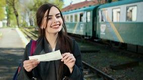 Een aantrekkelijke jonge vrouw reist door trein, bekijkt het gekochte kaartje voor een reis en zoekt het aantal van hem stock video