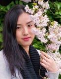 Een aantrekkelijke jonge vrouw stelt met een tak van mooie de lentebloemen royalty-vrije stock foto's
