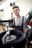 Een aantrekkelijke jonge werktuigkundige glimlacht terwijl het werken op een autoworkshop stock afbeeldingen