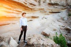 Een aantrekkelijke mens bevindt zich in het midden van een zandsteengroeve en kijkt zorgvuldig in de afstand stock fotografie