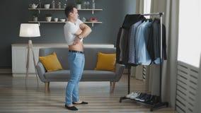 Een aantrekkelijke mens denkt om zich op verschillende kleren in een kleedkamer voor een commerciële vergadering of een datum te  stock videobeelden