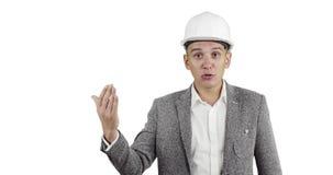 Een aantrekkelijke mens in een wit bouwhelm en een kostuum bekijkt de camera en spreekt stock videobeelden