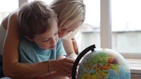 Een aantrekkelijke moeder van het Kaukasische behoren tot een bepaald ras gebruikt een bol om haar jonge zoon de landen van de we stock video