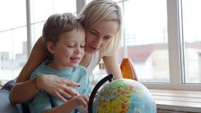 Een aantrekkelijke moeder van het Kaukasische behoren tot een bepaald ras gebruikt een bol om haar jonge zoon de landen van de we stock videobeelden