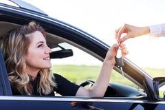 Een aantrekkelijke vrouw in een auto krijgt de autosleutels Huur of aankoop van auto stock afbeelding
