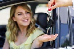 Een aantrekkelijke vrouw in een auto krijgt de autosleutels Huur of aankoop van auto stock fotografie