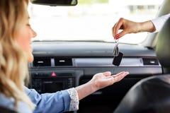 Een aantrekkelijke vrouw in een auto krijgt de autosleutels Huur of aankoop van auto stock foto's