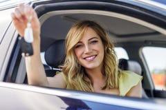 Een aantrekkelijke vrouw in een auto krijgt de autosleutels Huur of aankoop van auto stock foto