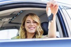 Een aantrekkelijke vrouw in een auto krijgt de autosleutels Huur of aankoop van auto royalty-vrije stock fotografie