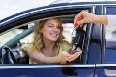 Een aantrekkelijke vrouw in een auto krijgt de autosleutels Huur of aankoop van auto royalty-vrije stock foto