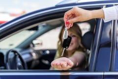 Een aantrekkelijke vrouw in een auto krijgt de autosleutels Huur of aankoop van auto royalty-vrije stock afbeeldingen