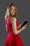 Een aantrekkelijke vrouw die, die en een tablet glimlachen houden Stock Foto