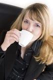 Een aantrekkelijke vrouw in een zwart kostuum dat een kop van koffie drinkt Stock Foto