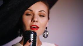 Een aantrekkelijke vrouw in grote zwarte elegante hoed grijpt mic en begint te zingen Heldere verlichting stock footage
