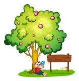 Een aapzitting onder de boom naast de lege houten raad Stock Afbeeldingen