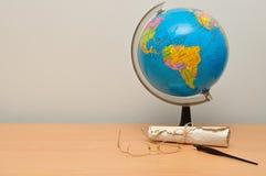 Een aardebol met een rol, glazen en een vulpen Stock Afbeelding